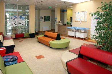 korytarz w poradni - kolorowe kanapy i kwiaty