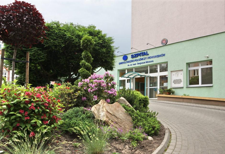 wejście do szpitala - budynek, z lewej strony kwiaty