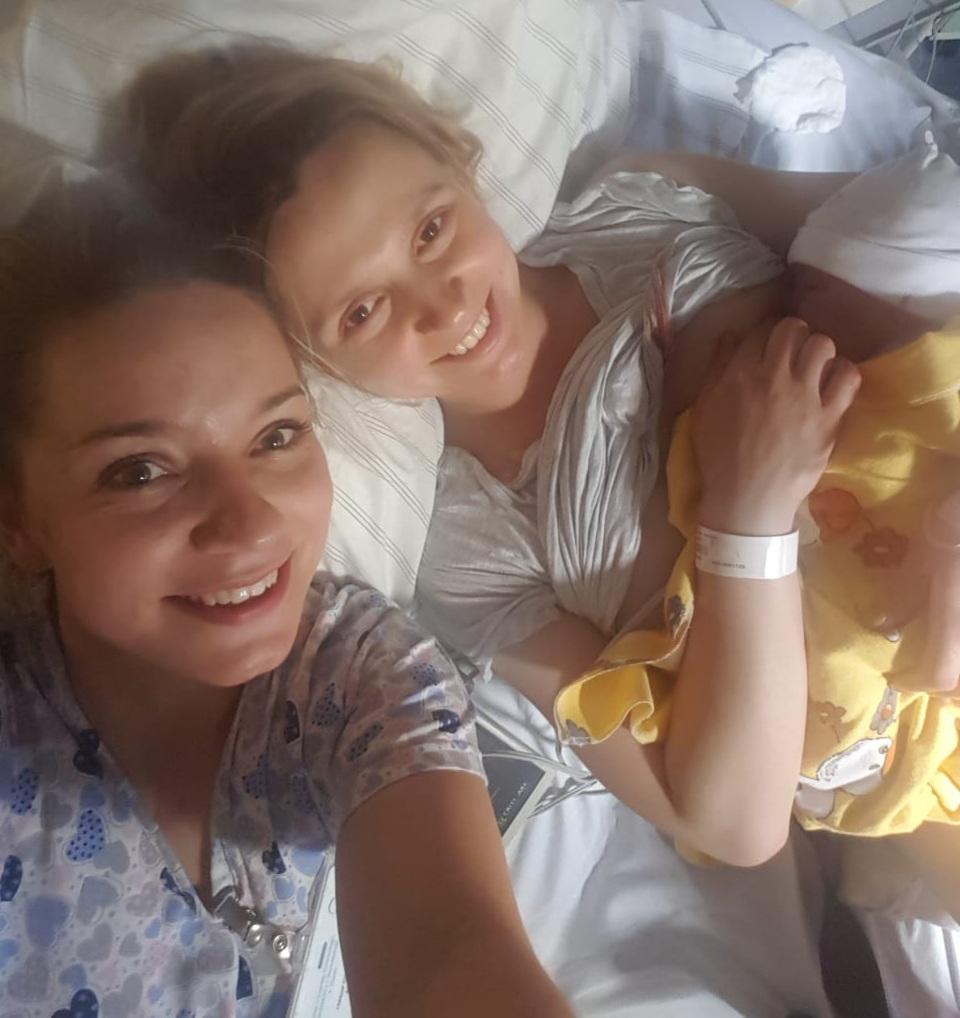 mama karmiąca nowo narodzone dziecko i uśmiechnięta położna